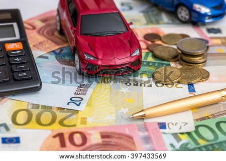 luxury toy car on Euro cash with calculator and pen - stock photo
