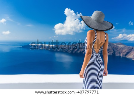 Luxury travel vacation woman looking at view on Santorini famous Europe travel destination. Elegant young lady living fancy jetset lifestyle wearing dress on holidays. Amazing view of sea and Caldera.