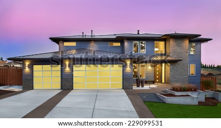 Luxury Two-Story Home Exterior at Sunset with Two Car Garage - stock photo