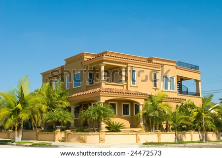 Luxury Two Story Stucco House with Tropical Landscaping and Blue Sky