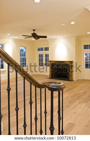 luxury unfurnished livingroom with fireplace and stair rail - stock photo