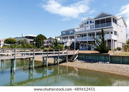 Luxury vacation beach houses on the inter coastal canal water at low tide, North Carolina.