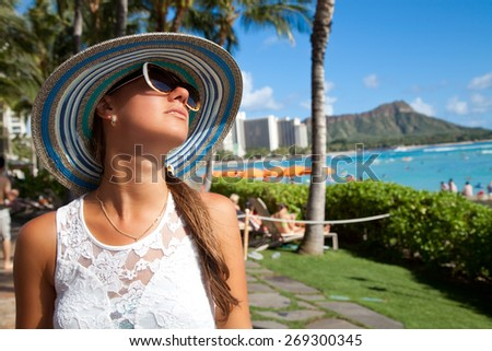 Luxury vacation beautiful woman in straw hat relaxing on Waikiki beach, Honolulu city, Oahu Island, Hawaii, USA with Diamond Head Mountain in the background. Relaxation concept for summer vacations. - stock photo