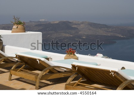 luxury villa view of greek island harbor with cruise ships and plants lounge chairs hotel