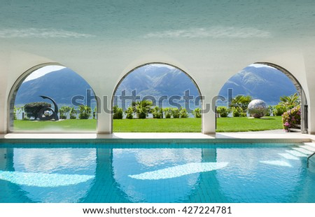 Luxury villa with indoor swimming pool, arched windows - stock photo