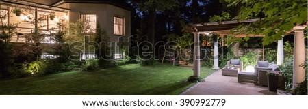 Luxury villa with patio in garden at night - stock photo