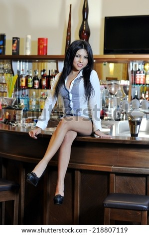 Luxury, vip, nightlife, party concept: beautiful young latin woman in sensual dress with high heels smiling and sitting on classic bar counter with bottles in blurred background