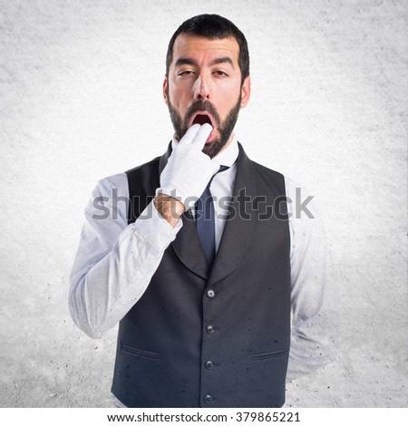 Luxury waiter doing vomiting gesture - stock photo