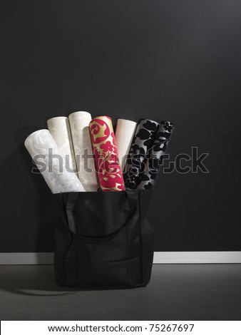 luxury wall paper rolls arranged in a black basket, copy space - stock photo