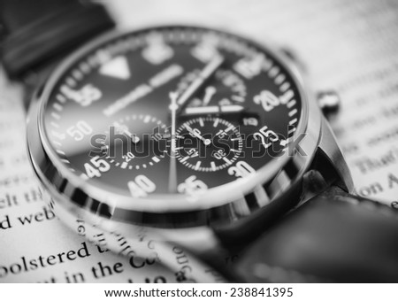Luxury watch up close on a newspaper in black and white  - stock photo