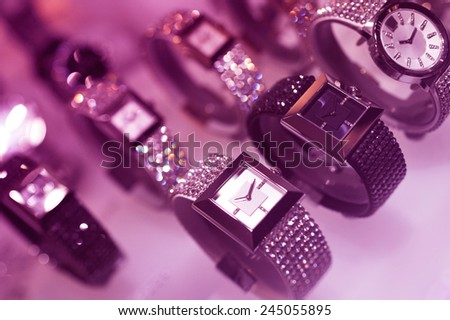Luxury watches on display in a jewelry store - LED violet color cast to give extra luxury feel. - stock photo