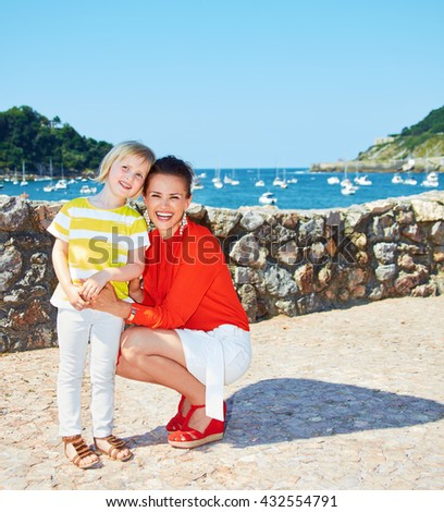Luxury weekend with family. Full length portrait of happy mother and child in front of the beautiful scenery overlooking lagoon with yachts