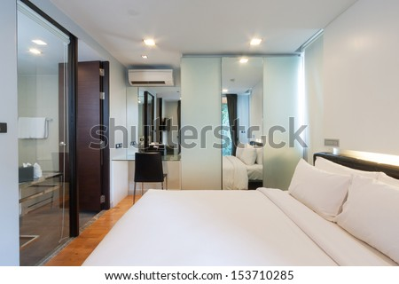 luxury white bedroom with bathroom in apartment. - stock photo
