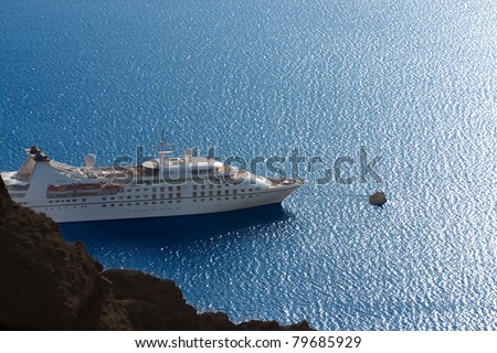 luxury white cruise ship on a clear day with calm seas and blue sky on the greek island of santorini - stock photo