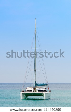 Luxury white sail catamaran boat in the sea with blue sky - stock photo
