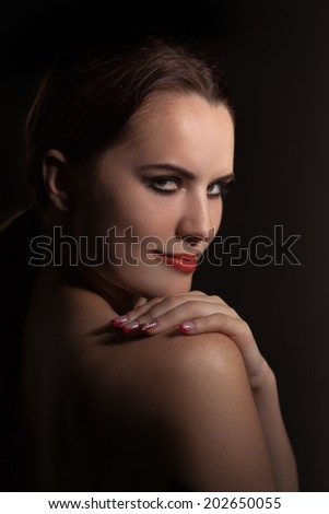 luxury woman looking over bared shoulder