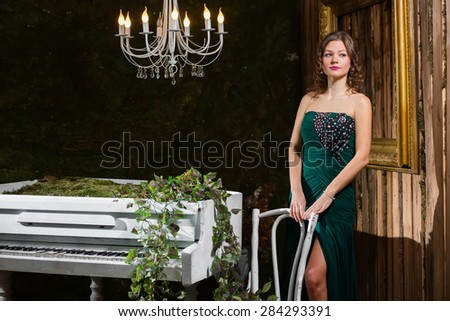 Luxury woman looking to the side, near the piano - stock photo