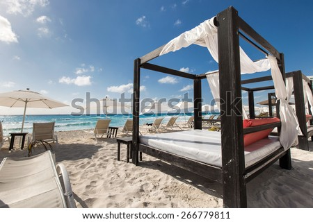 Luxury wooden lounge beds on a beautiful caribbean beach  - stock photo