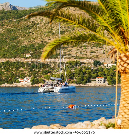 Luxury yacht sails on the Adriatic Sea coastline. Traveling near the island. The boat is sailing into the port. Dubrovnik, Croatia - stock photo