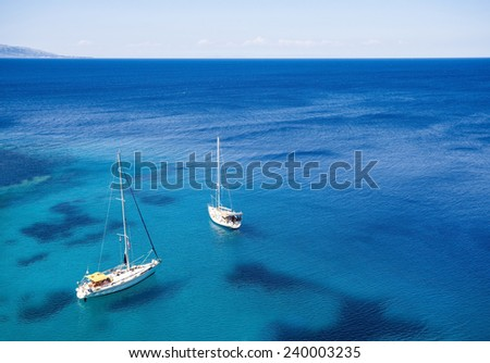 Luxury yachts in crystal clear sea waters - stock photo