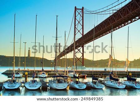 Luxury yachts under the 25 april bridge in Lisbon, Portugal - stock photo
