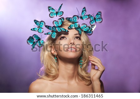 Luxury young woman with butterflies on her head. Beautiful stylish trendy girl. - stock photo