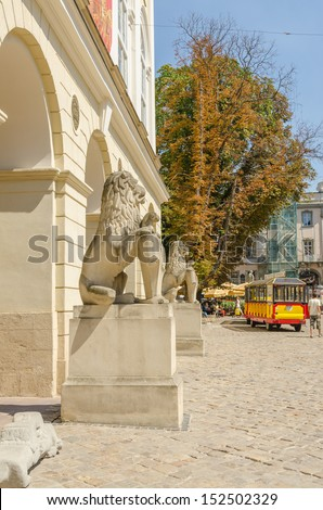 LVIV, UKRAINE - AUGUST 13: Lions' statue in front of Town Hall on the Rynok Square and sightseeing car train waiting for tourists on August 13, 2013 in Lviv, Ukraine.