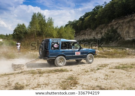 Lviv, Ukraine - August 23, 2015: Off-road vehicle brand Land Rover with burden overcomes the track on of sandy career near the city Lviv, Ukraine. - stock photo
