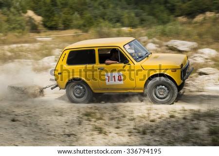 Lviv, Ukraine - August 23, 2015: Off-road vehicle brand VAZ- NIVA with burden overcomes the track on of sandy career near the city Lviv, Ukraine. - stock photo