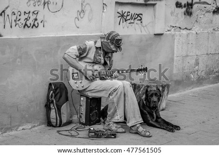 LVIV, UKRAINE - AUGUST 2016: Street musician playing rock hits of the electric guitar, sitting with a large black dog, near the walls of the house with graffiti on the old streets of Lviv