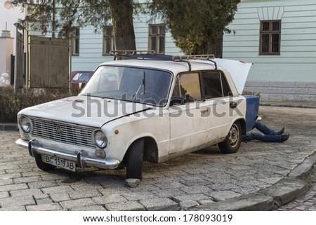 LVIV, UKRAINE - FEBRUARY 15 : An old car being repaired by a man on February 15, 2014 in Lviv, Ukraine. - stock photo