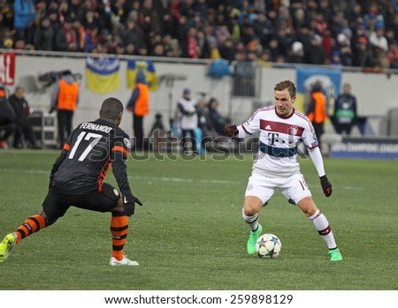 LVIV, UKRAINE - FEBRUARY 17, 2015: Mario Gotze of Bayern Munich (R) fights for a ball with Fernando of Shakhtar Donetsk during their UEFA Champions League game at Arena Lviv stadium - stock photo