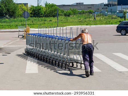 "LVIV, UKRAINE - JUL 05, 2015: Nested empty shopping carts being returned from a parking lot to ""METRO Cash & Carry"" store by an old worker naked to the waist. - stock photo"