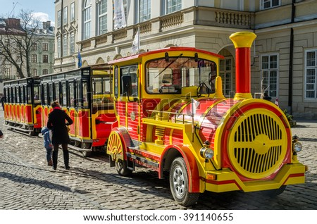 LVIV, UKRAINE - MARCH 2016: Yellow and red touring car in the form of a train with carriages waiting for tourists landing on a tour is a sunny day at the Market Square in Lviv, Ukraine