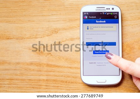 LVIV, UKRAINE - May 03, 2015: Hand holding white Samsung Smart Phone with Facebook Social Network Log In Screen, and women try create new account, on wooden background - stock photo