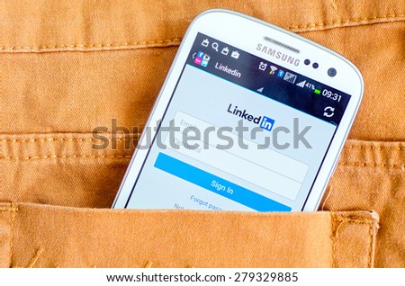 LVIV, UKRAINE - May 19, 2015: Hand holding white Samsung Smart Phone with LinkedIn social Network Log In Screen - stock photo