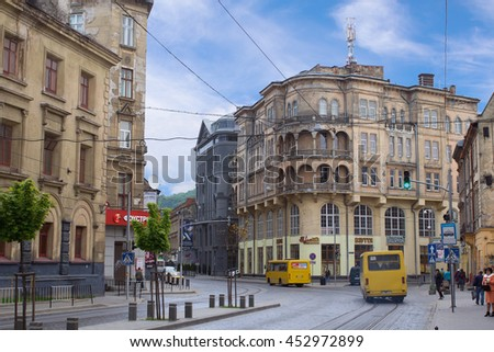 LVIV, UKRAINE - MAY 8, 2016:  One of the streets of Lviv in the afternoon: shuttle buses on the road, people waiting for transport and old-style buildings, Ukraine - stock photo