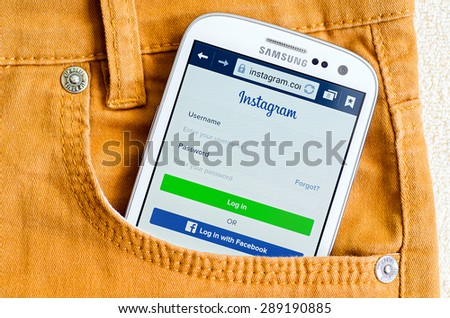 LVIV, UKRAINE - May 19, 2015: White Samsung Galaxy Smart Phone with Instagram social network Log In Screen in orange jeans pocket - stock photo