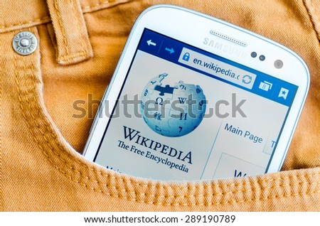 LVIV, UKRAINE - May 19, 2015: white Samsung Smart Phone with Wikipedia main page screen in the pocket of orange jeans - stock photo