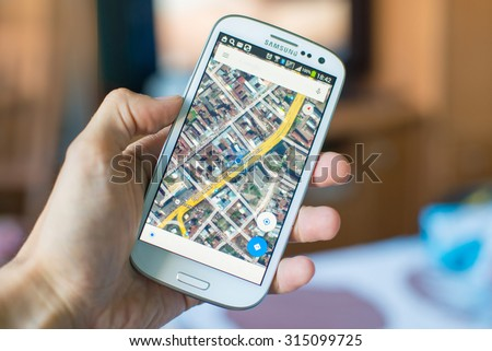LVIV, UKRAINE - Sept 09, 2015: Hand holding white Samsung Smart Phone with Google map application - stock photo