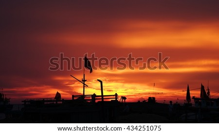 LY SON ISLAND, VIETNAM - JUNE 2016 : Beautiful sunset over boats on the sea of Ly Son island, Quang Ngai province, Vietnam. Flag and crane waving in the red sky. Revolution abstract. Sihouette.