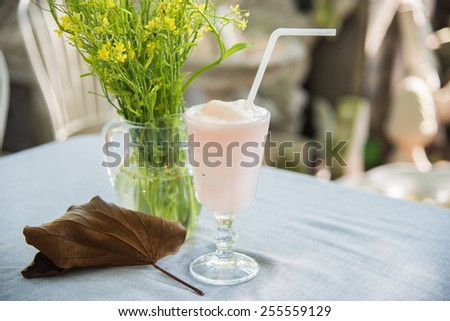 Lychee smoothie in glass with yellow flower and golden leaf decorated