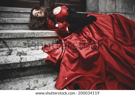 Lying and bleeding woman in a red Victorian dress - stock photo