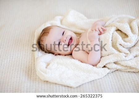 Lying baby girl in a blanket - stock photo
