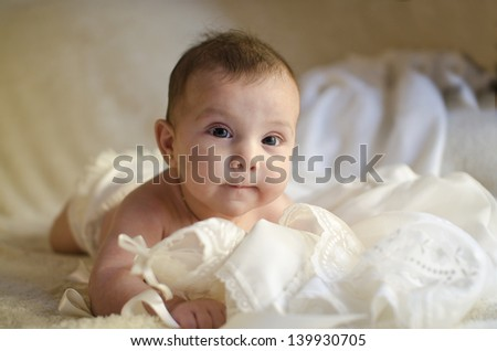 Lying baby on clothes, looking at the view. - stock photo
