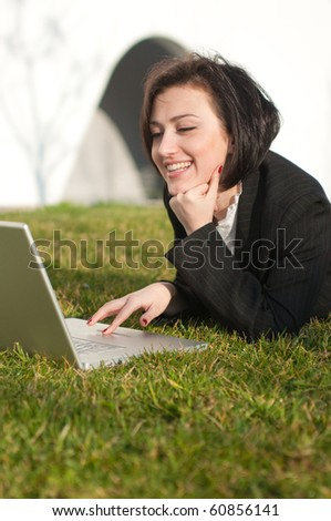 Lying brunette businesswoman with a laptop - stock photo