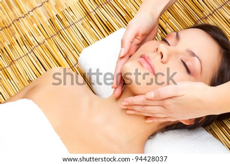 lying brunette woman receiving massage of head - stock photo