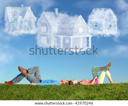 lying couple on grass and dream three cloud houses collage - stock photo