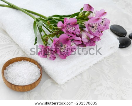 Lying down branch pink orchid on towel with stones ,salt in bowl and white lace  - stock photo