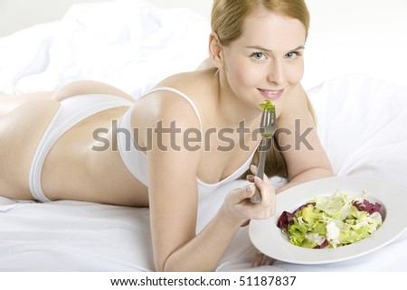 lying down woman eating salad - stock photo
